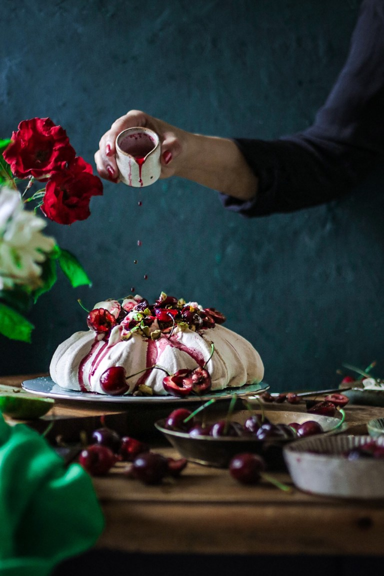 Meringue with poached cherries, whipped cream and pistachio